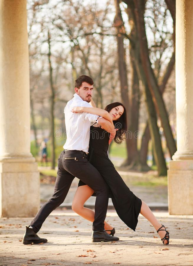 Passionate elegant young couple latino dancers in tango in the park royalty free stock images