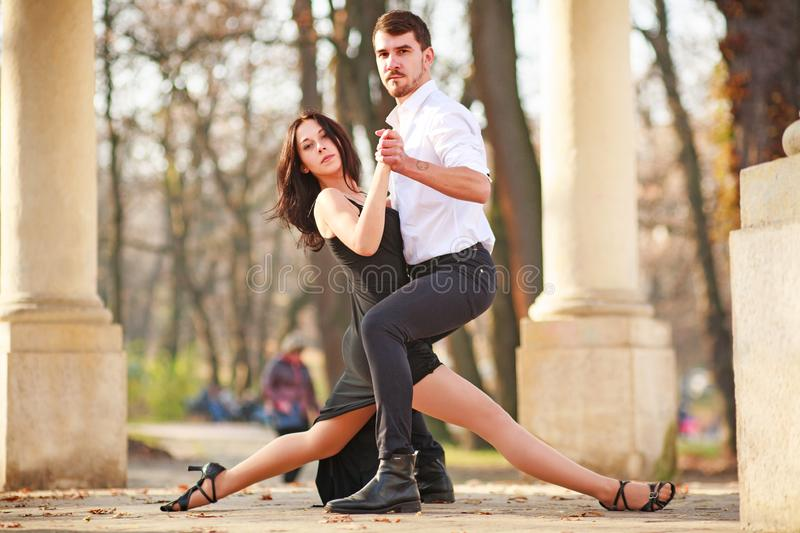Passionate elegant young couple latino dancers in tango in the park royalty free stock photos