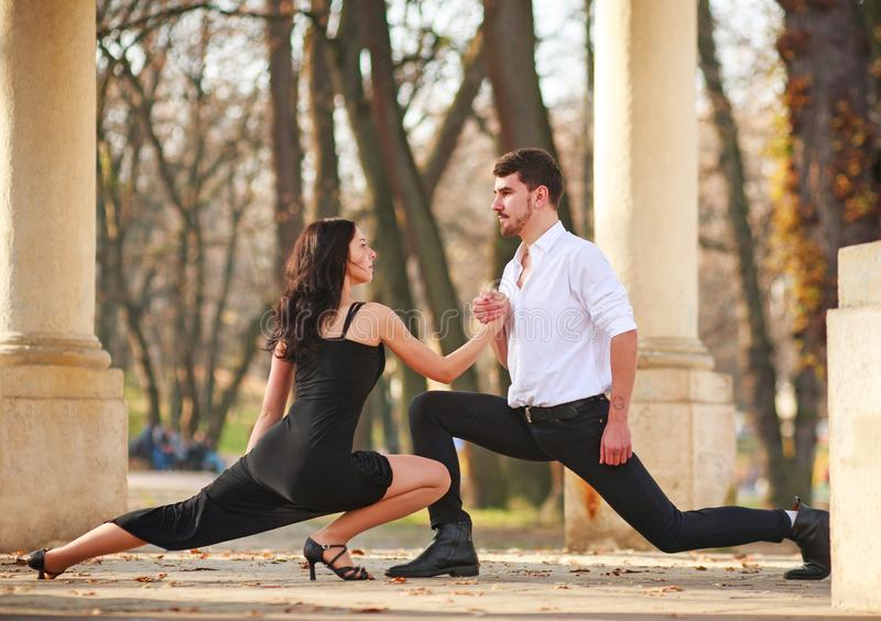 Passionate elegant young couple latino dancers in tango in the park royalty free stock image