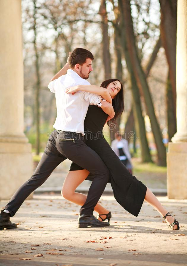 Passionate elegant young couple latino dancers in tango in the park stock images