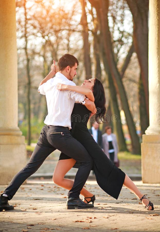 Passionate elegant young couple latino dancers in tango in the park stock photography