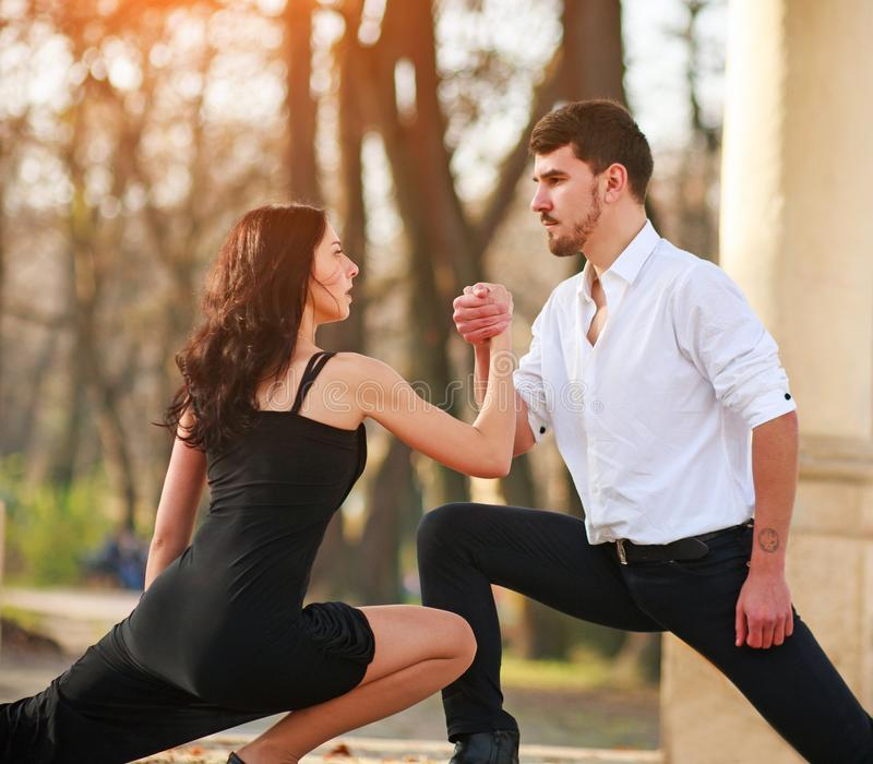 Passionate elegant young couple latino dancers in tango in the park royalty free stock photography