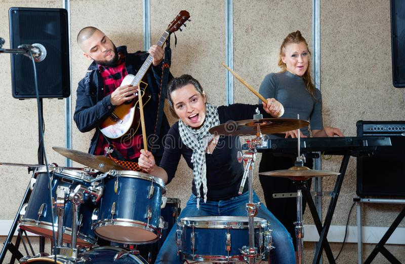Passionate emotionele vrouwelijke drummer met haar bandmaten die in de repetitiezaal oefenen stock afbeeldingen