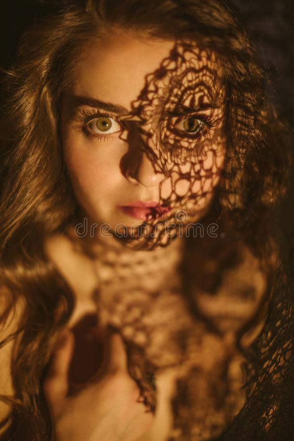 Passionate eyes glance. Emotional expressive portrait of a beautiful girl with lace shadows on her face royalty free stock photos