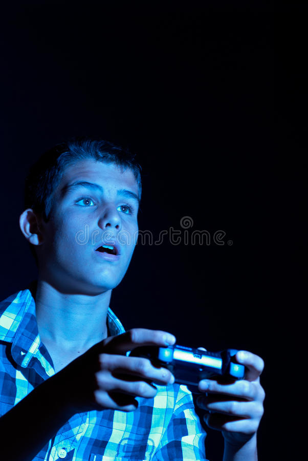 Passionate gamer. Teen with deranged facial expression while passionately gaming royalty free stock photo