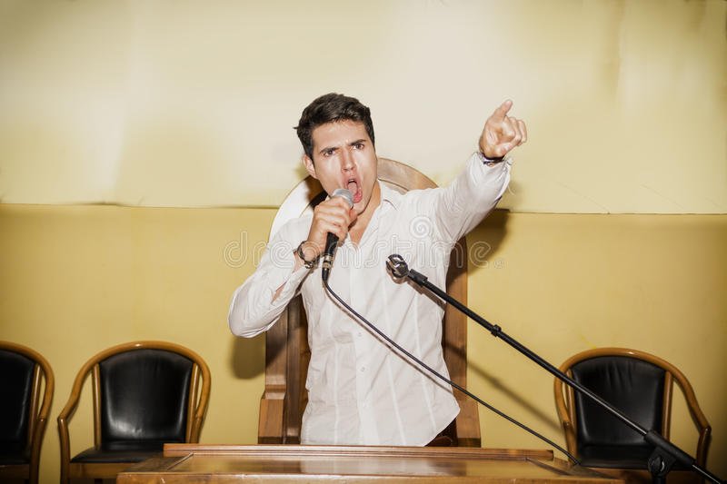 Passionate Man Speaking into Microphone in Meeting stock images