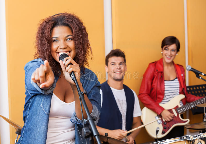 Passionate Singer Pointing While Performing In Recording Studio. Portrait of passionate female singer pointing while performing in recording studio royalty free stock photos