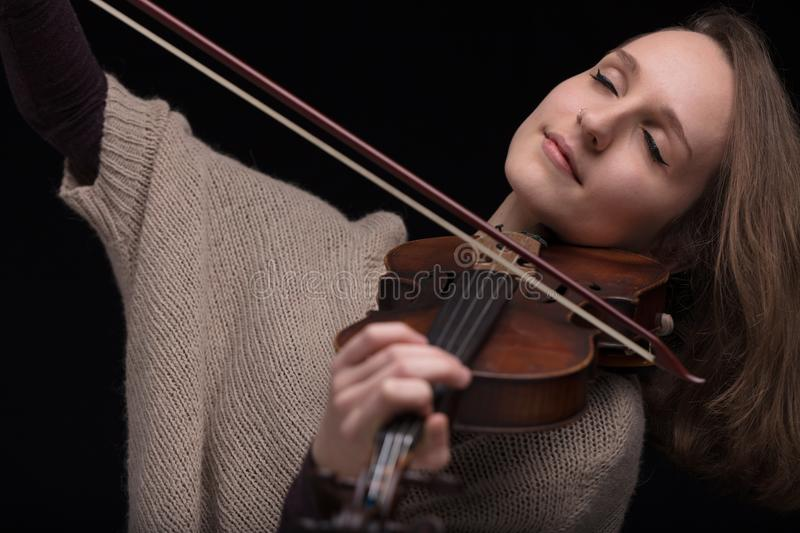 Passionate violin musician playing on black background. Serious and concentrated violin player - portrait of a woman on black background playing strings stock images