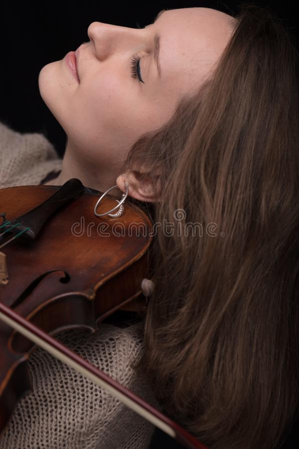 Passionate violin musician playing on black background. Serious and concentrated violin player - portrait of a woman on black background playing strings royalty free stock images