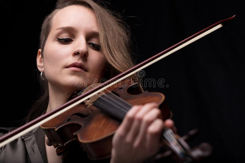 Passionate violin musician playing on black background. Serious and concentrated violin player - portrait of a woman on black background playing strings stock photography