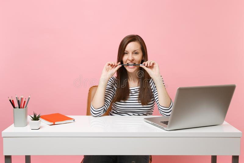 Passionate woman in casual clothes gnawing hold pencil in teeth sit work at white desk with contemporary pc laptop. Isolated on pastel pink background royalty free stock photos