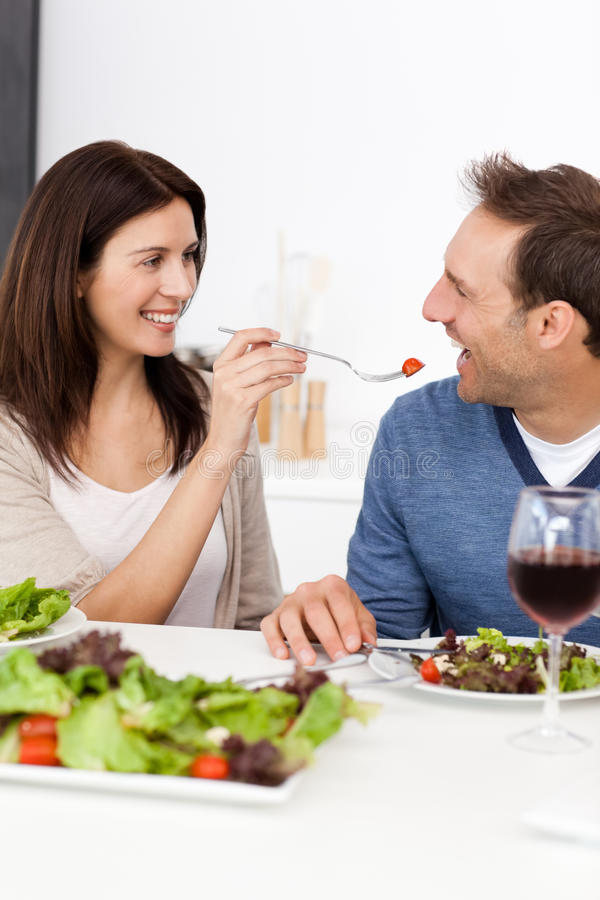 Passionate Woman Giving A Tomato To Her Husband Stock Image