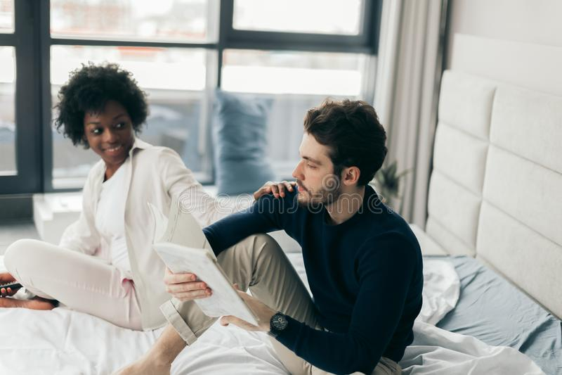 Interracial young couple relaxing and having fun on bed. African woman royalty free stock images