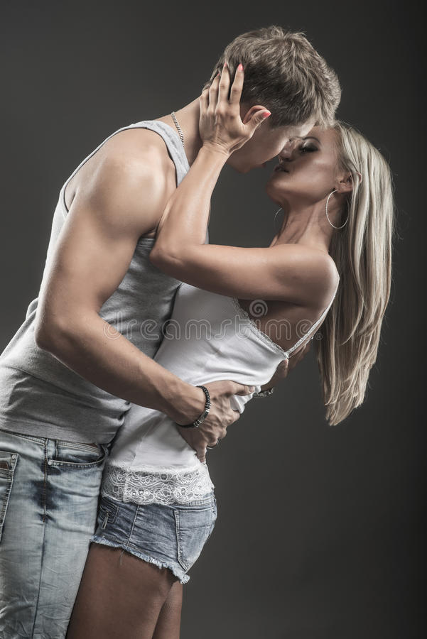 Passionate young couple in love on dark stock photos