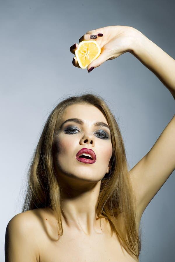 Passionerad blond stående för ung kvinna med apelsinen arkivbild