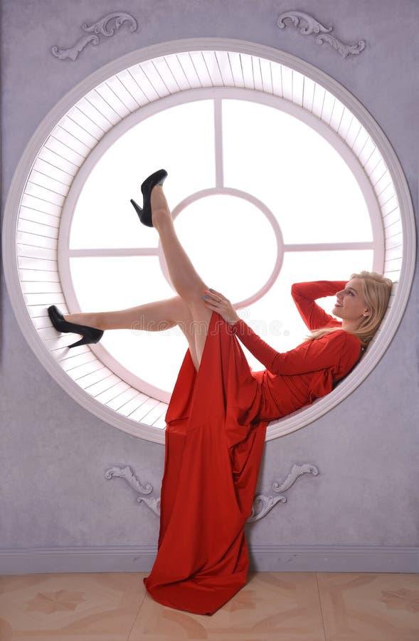 Passionerad flicka i röd klänning med öppet tillbaka vid fönstret arkivfoto
