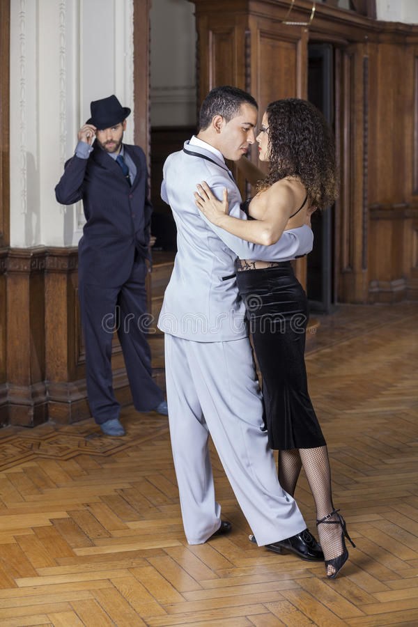 Passionerade tangodansare som utför medan man som ser dem arkivfoto
