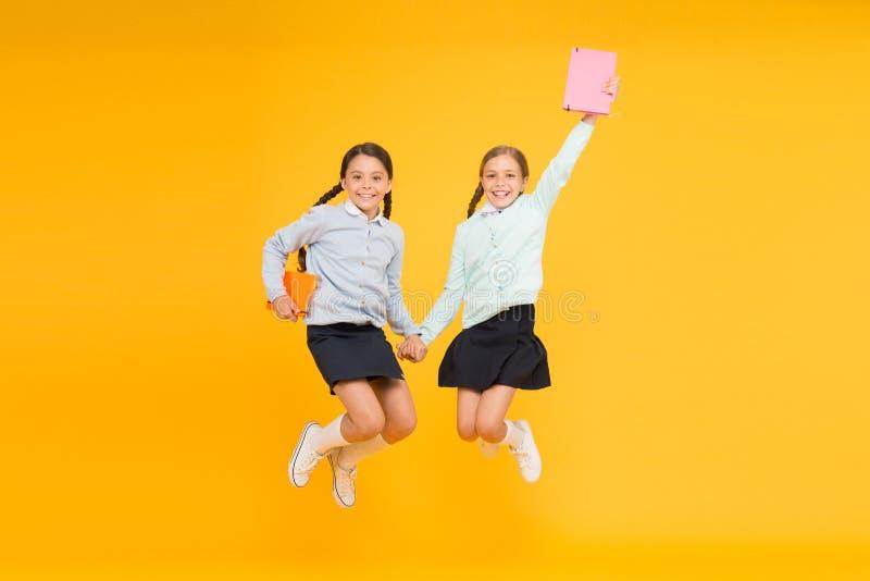 Passionerat om böcker Lyckliga små flickor som hoppar med böcker på gul bakgrund Gulliga småbarn som ler med fotografering för bildbyråer