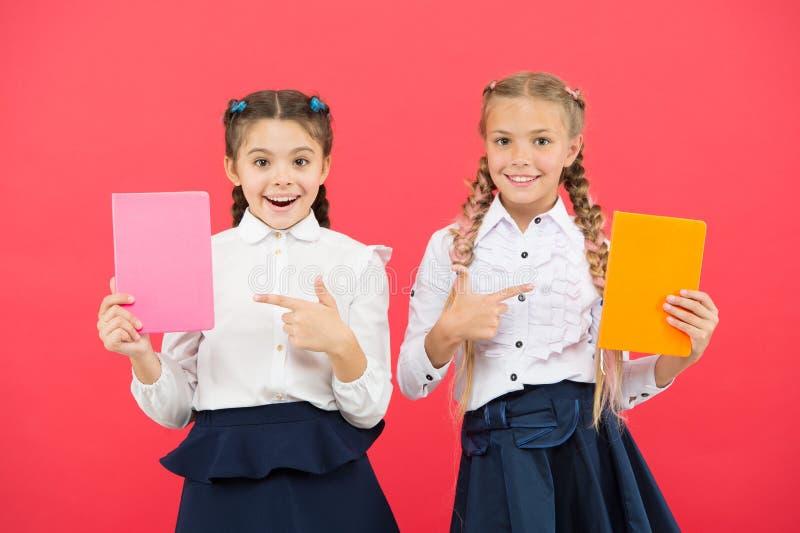 Passionerat om böcker Lyckliga små flickor som pekar på böcker på röd bakgrund Gulliga småbarn som ler med arkivfoto