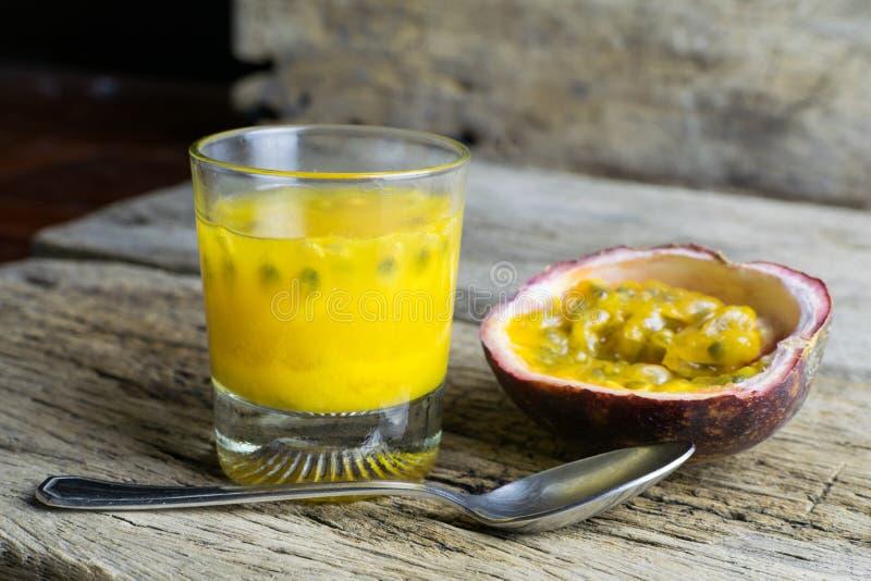 Passionfrukter med exponeringsglas av passionfruktfruktsafter på trä arkivfoto