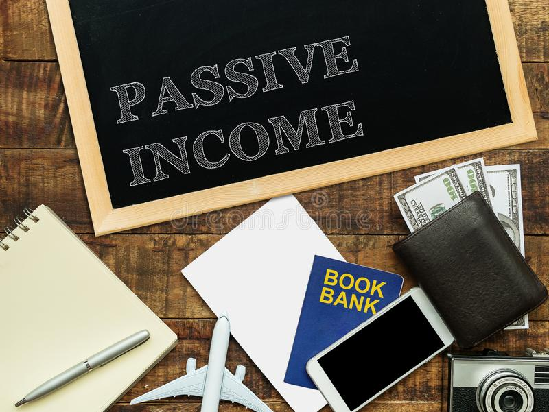Passive income, financial concept. text PASSIVE INCOME on chalkboard at the wooden table with book bank , money wallet , banknote royalty free stock images