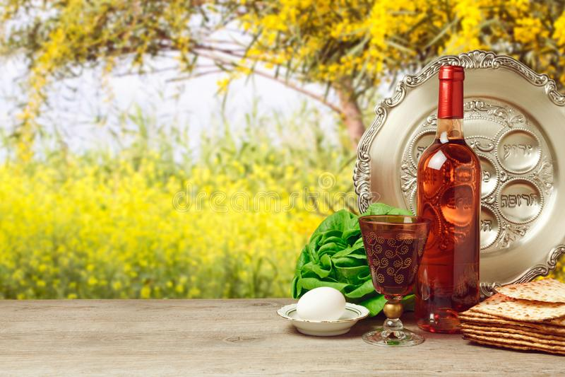 Passover background with wine bottle and matzoh. Passover background with wine bottle, matzoh, egg and seder plate over beautiful nature. Hebrew text translation royalty free stock image