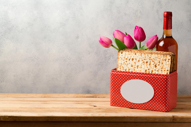 Passover celebration concept with matzoh, wine and tulip flowers over bright background. With copy space royalty free stock image