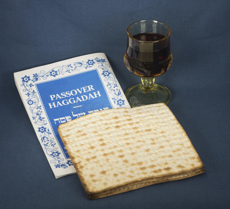 Passover Haggadah, Matzo, and Glass of Wine. Passover haggadah, matzo, and light yellow glass of wine on a blue cloth background royalty free stock photos