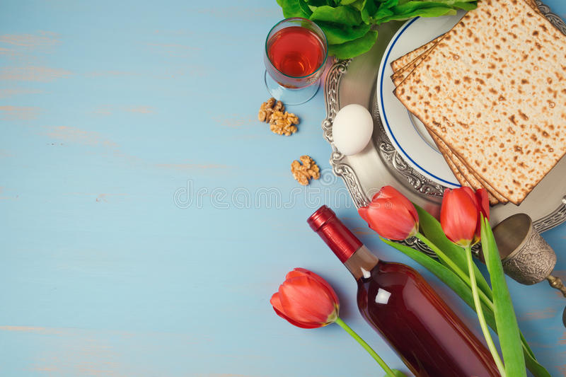 Passover holiday concept seder plate, matzoh and tulip flowers on wooden background. Top view from above royalty free stock photography