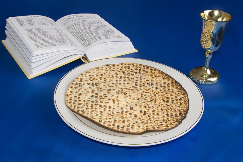 Passover Matzo. Passover holiday table with round Matzo (Jewish Bread), golden wine glass and prey book stock photos
