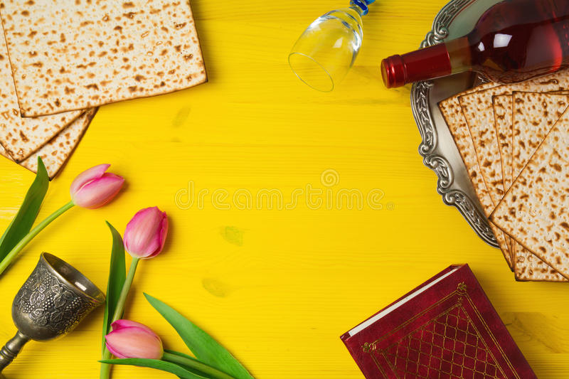 Passover Pesah celebration with matzoh, tulip flowers and wine bottle on yellow wooden background. View from above stock photo