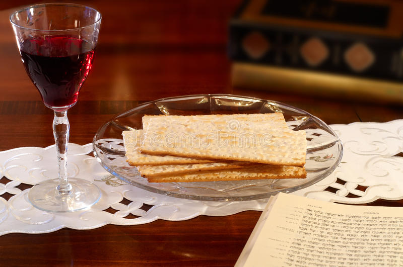 Passover tableau. Passover elements of wine and matzoh on a table with Hebrew Old Testament open to the Passover passage in Exodus stock photo