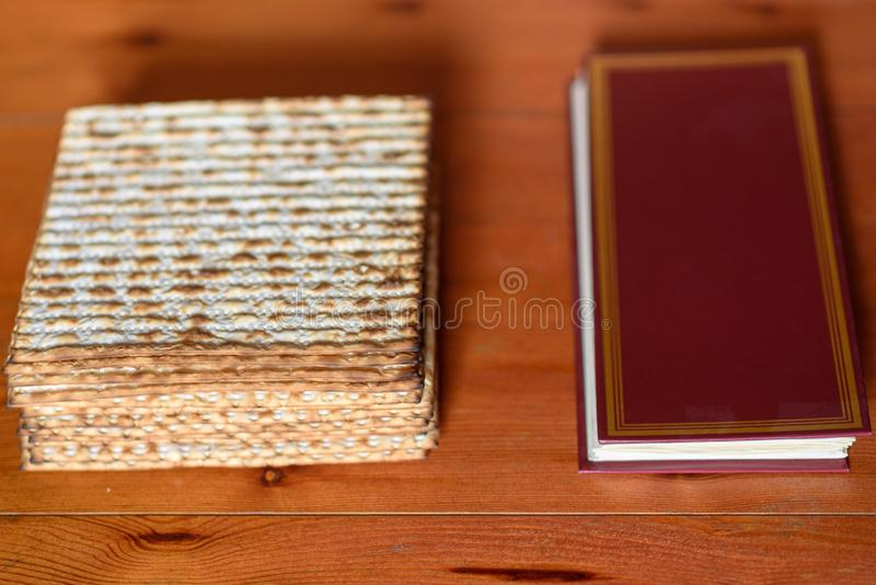 Passover. Traditional seder table set for a Jewish Festive meal matzah and Passover Haggadah. Pack of matzah or matzo or or matza and Passover Haggadah on a stock image