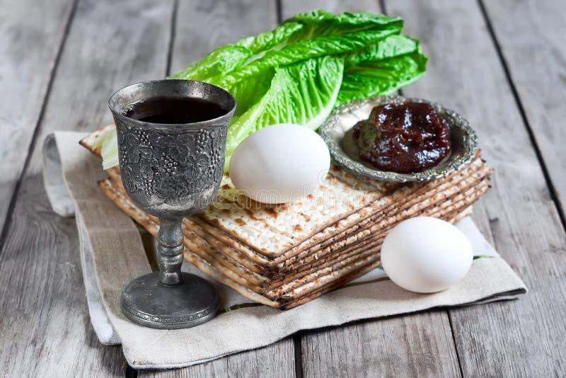 Passover. Wine, egg, bitter salad leaves, matzot and haroset - traditional jewish passover celebration elements royalty free stock images