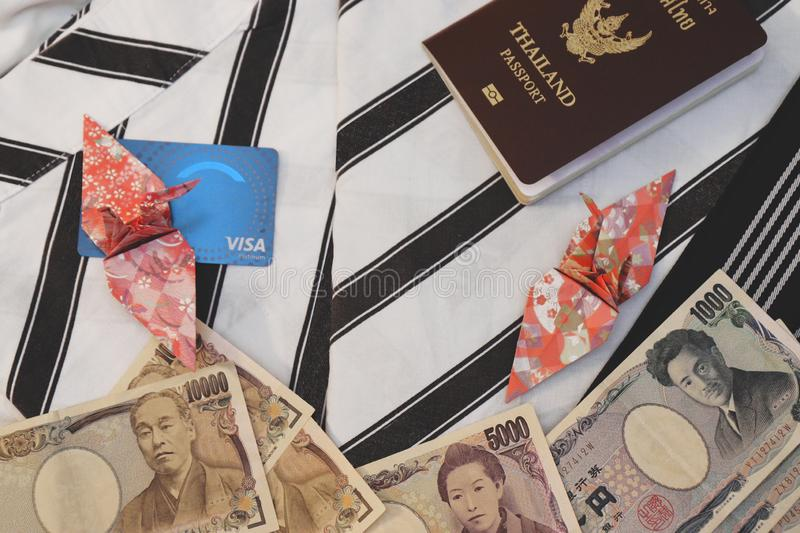 Passport,banknotes, credit card and origami paper birds place on japanese pajamas call as yukata stock photography