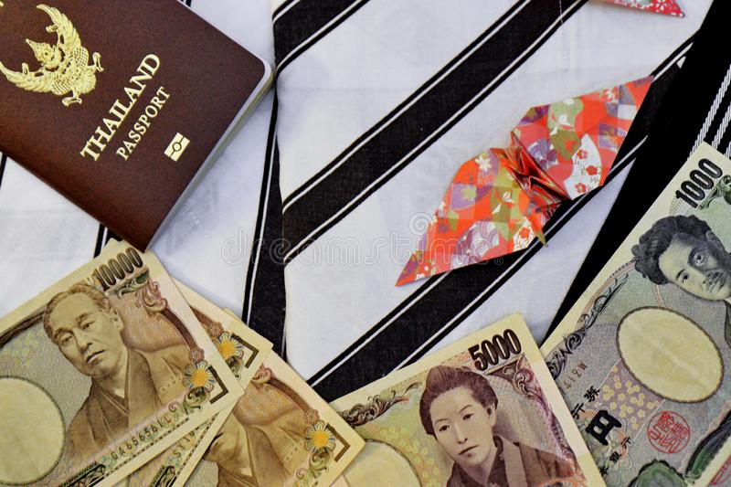 Passport,banknotes, credit card and origami paper birds place on japanese pajamas call as yukata. Passport,money banknotes, credit card and origami paper birds royalty free stock photo