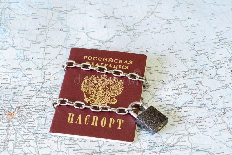 Passport of a citizen of the Russian Federation in a metal chain on the lock on the background of the geographical map of Russia stock photo