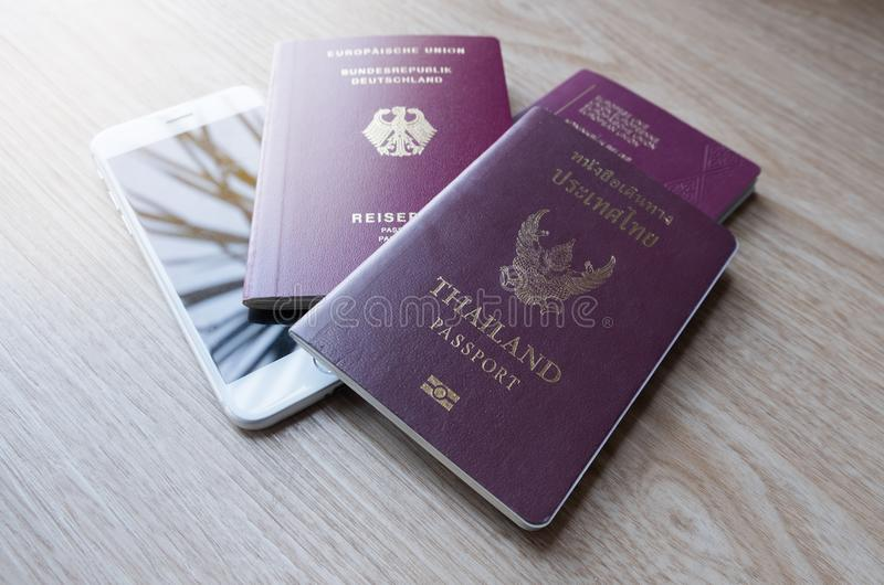 Passport of Germany, Thailand, and Belgium with white cellphone. On wooden table stock image