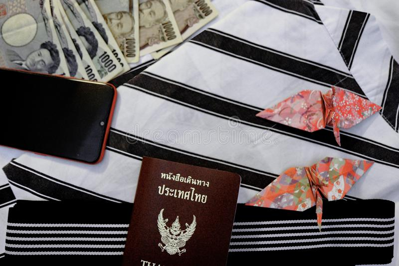 Passport,mobile phone,banknotes, credit card and origami paper birds place on japanese pajamas call as yukata. Passport,mobile phone,money banknotes, credit card stock images