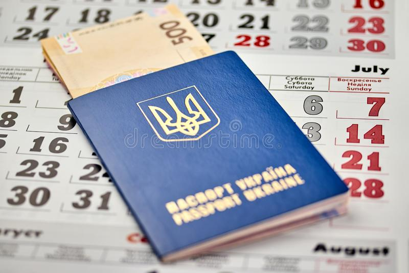 Passport with national currency paper money close up view of cash on a calendar background. Passport with national currency paper money close-up view of cash on stock photos