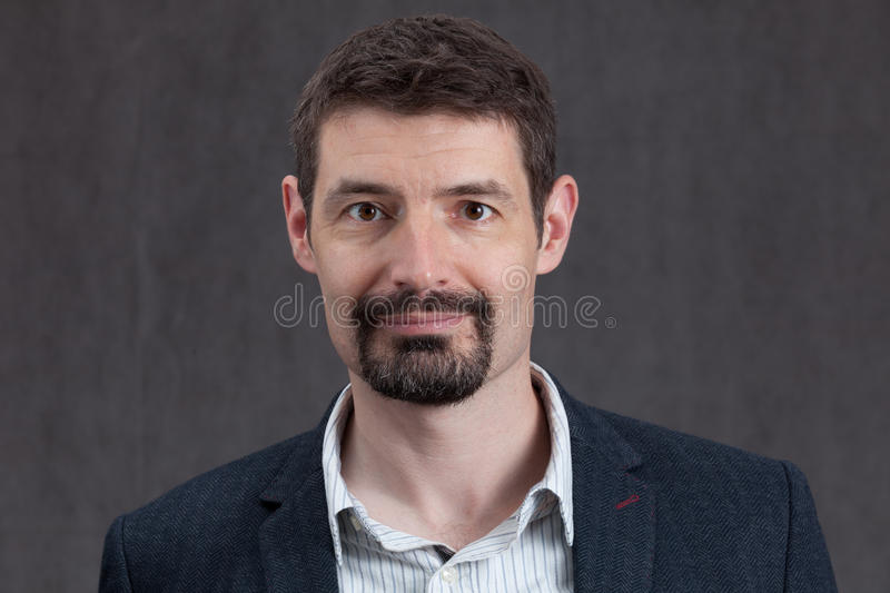Passport photo of forties man with a goatee beard and mustache. An adult male in his early forties with a goatee beard wearing a jacket and shirt. He is smiling royalty free stock images
