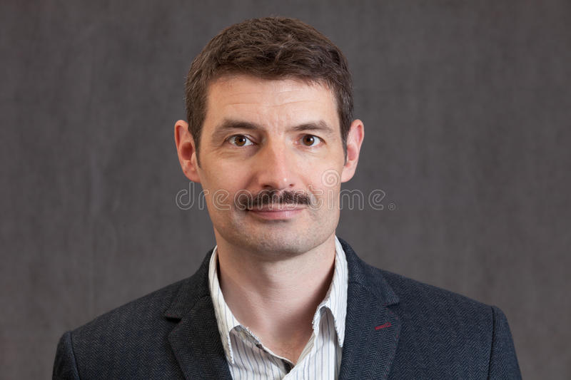 Passport photo of a smiling forties man with a short mustache. An adult male in his early forties with a 'movember' mustache wearing a jacket and shirt. He is stock image
