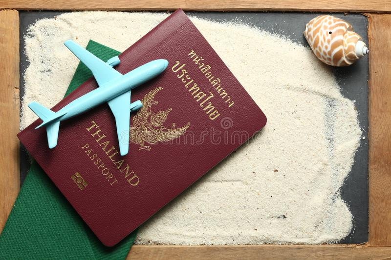 Passport and plane scene. Thailand passport with blue color jet plane toy model put on sand surface represent the tourism and travel industry concept related royalty free stock photography