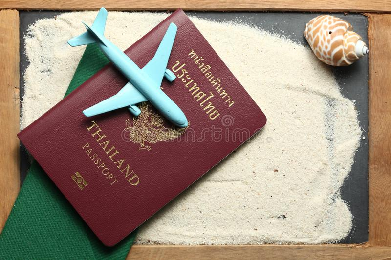 Passport and plane scene. Thailand passport with blue color jet plane toy model put on sand surface represent the tourism and travel industry concept related royalty free stock photos