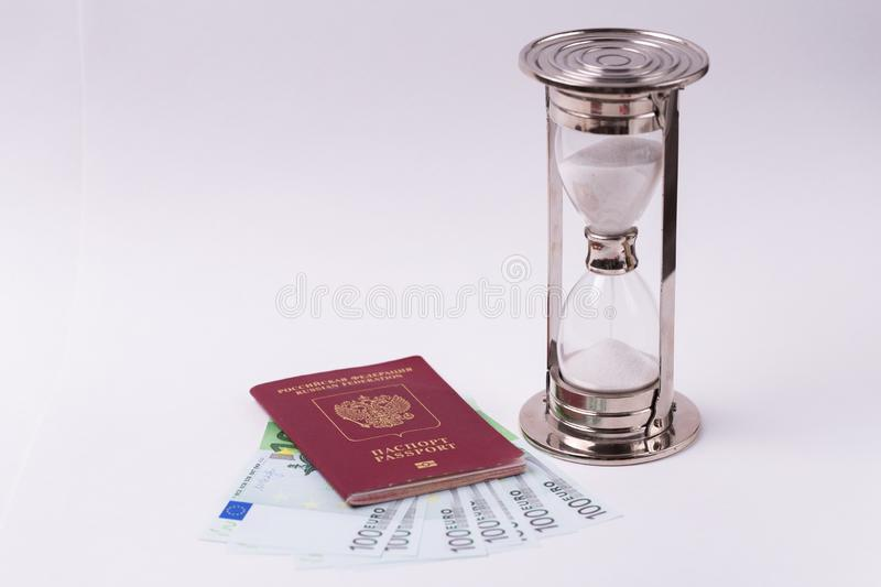 Passport of the Russian Federation with euro banknotes and hourglass on a white background stock photo