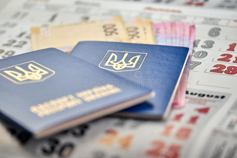 Passports with national currency paper money close up view of cash on a calendar background. Passports with national currency paper money close-up view of cash royalty free stock photography