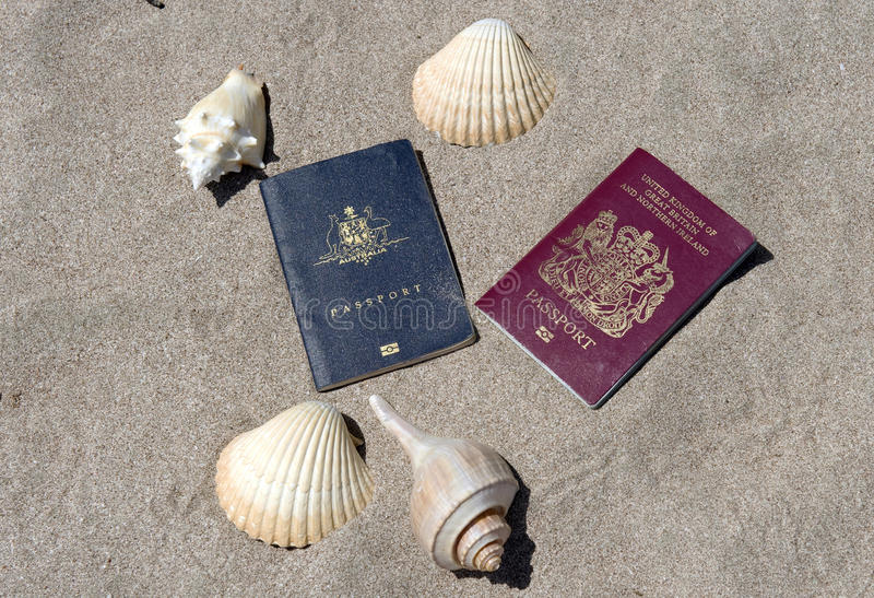 Passports on sandy tropical beach with shells royalty free stock photos