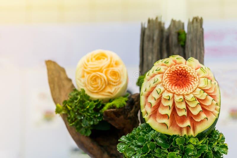 Pastèque colorée et belle et cantaloup découpés ou sculptés sur la feuille verte image stock