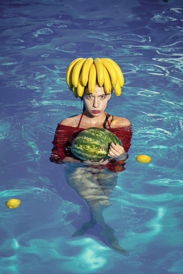 Pastèque de prise de fille dans l'hôtel de tourisme de piscine - goûtant les fruits frais tropicaux - vacances d'été images libres de droits