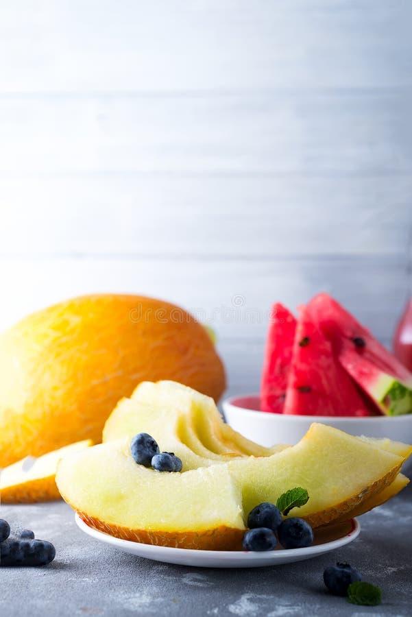Pastèque et melon coupés en tranches mûrs sur le gris photo libre de droits